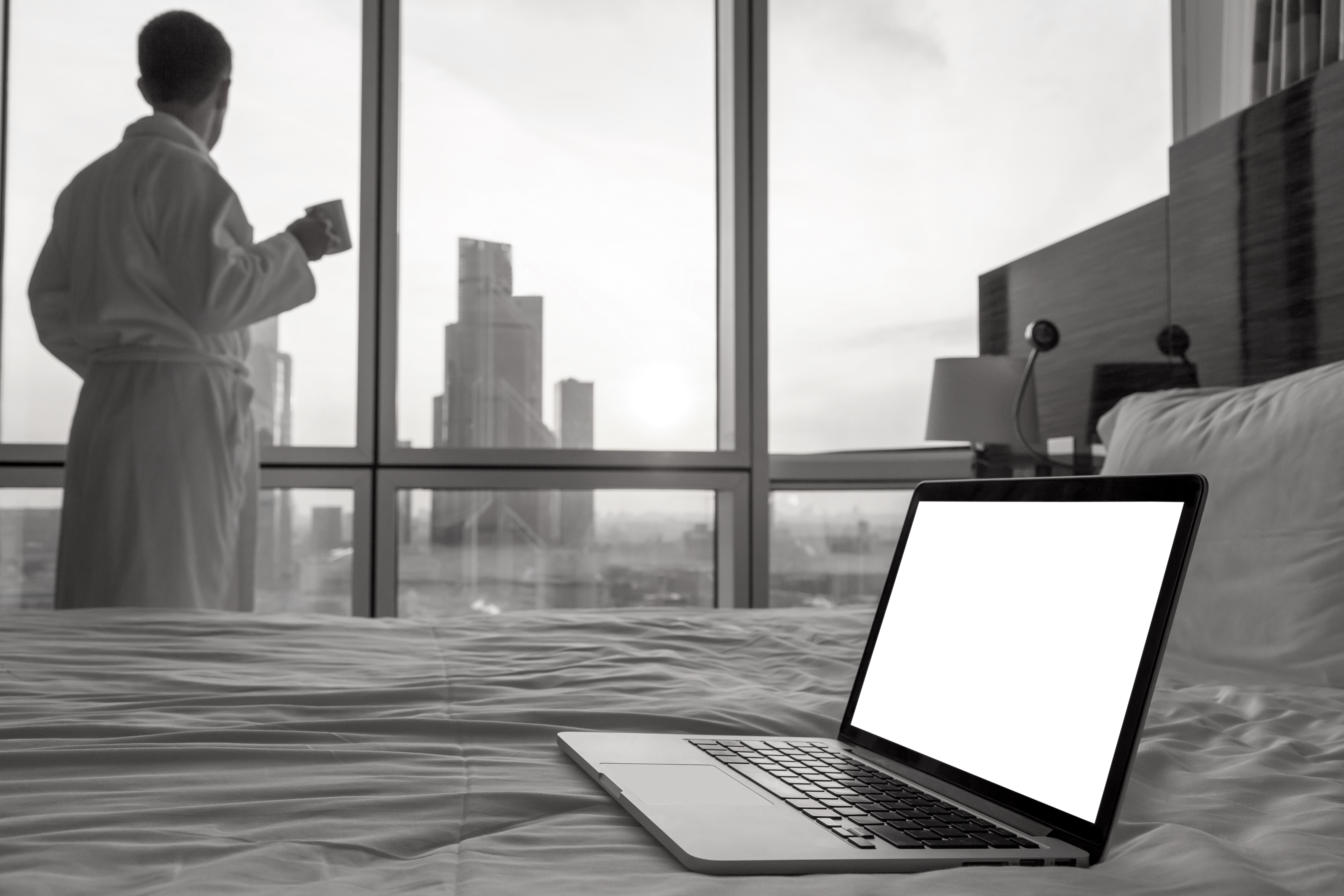Focus On Laptop Computer With Copy Space Blank Screen On The Bed. Young Businessman In White Bath Robe Standing At Window With Cup Of Coffee Looking At Sunset City View
